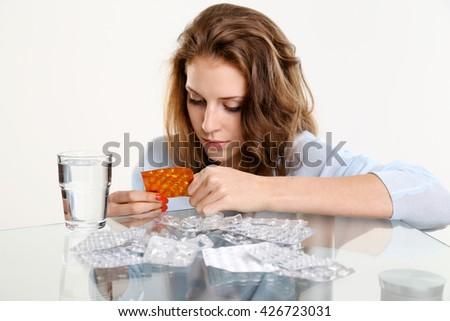Yong woman reading pills label  - stock photo