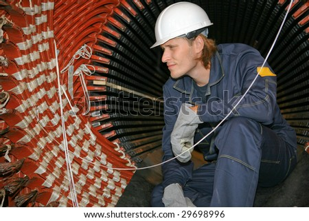 Yong worker in uniform is inspecting the coil winding of a transformer - stock photo