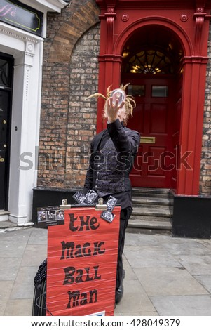 YORK, ENGLAND - 27 MAY 2016 - Unidentified street performer, dressed all in black, fascinates people with his magic ball performance. His crystal ball clearly shows his face reflected upside down,