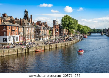 York, United Kingdom - August 7, 2015: View over the River Ouse to the pedestrian area in the city of York, UK.York is a historic walled city in North Yorkshire, England. - stock photo