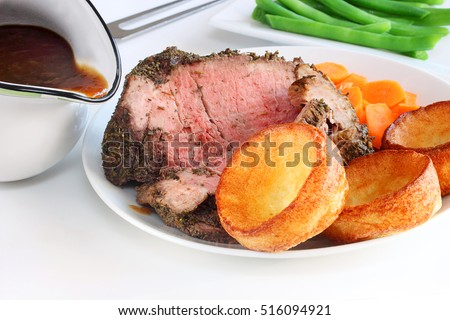 Yorkshire mini puddings served with medium rare roast beef and gravy, a traditional English Sunday meal