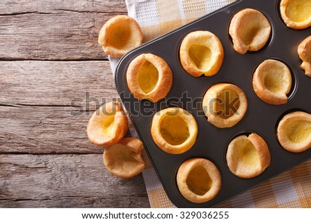 Yorkshire puddings in baking dish close up on the table. horizontal top view - stock photo