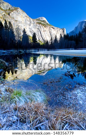 Yosemite icy winter landscape with beautiful clear reflections in the Merced River flowing through the valley - stock photo