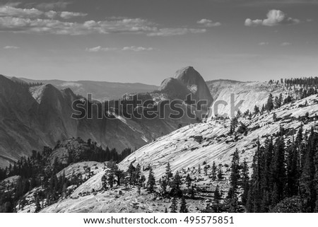 Yosemite Park  panoramic view of granite formations and pines in a sunny cloudy day at Olmsted Point