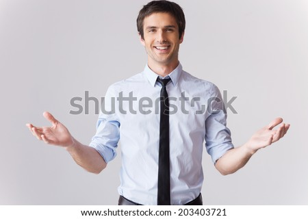 You are always welcome! Handsome young man in shirt and tie gesturing and smiling while standing against grey background  - stock photo