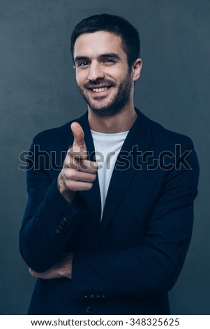 You are awesome! Cheerful young man pointing you and looking at camera while standing against grey background  - stock photo