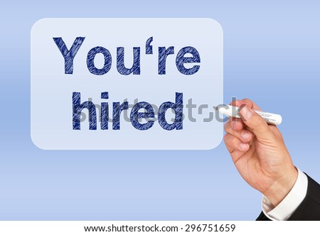 You are hired - Businessman writing text on blue screen - stock photo
