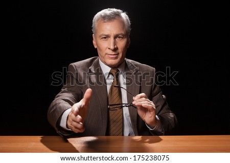 You are hired! Cheerful senior man in formalwear sitting at his working place and stretching out his hand for shaking while isolated on black background  - stock photo