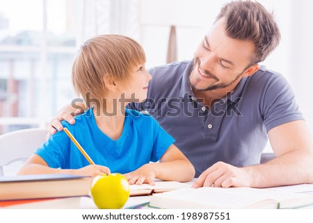 You are so smart! Cheerful young father helping his son with homework while sitting at the table together  - stock photo