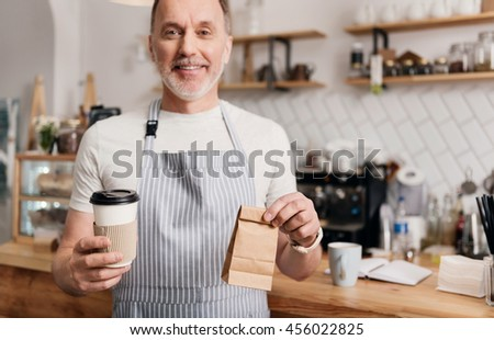 You are welcome. Smiling and cheerful male cafe worker in apron holding coffee to go and little lunch bag - stock photo