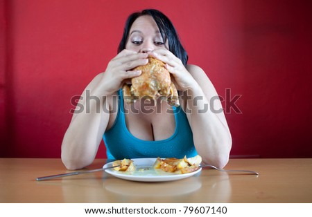 You are what you eat. Overweight woman stuffing herself with chicken. - stock photo