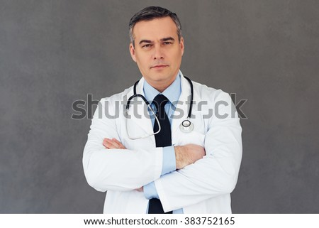 You can rely to this doctor. Mature male doctor keeping arms crossed and looking at camera while standing against grey background - stock photo