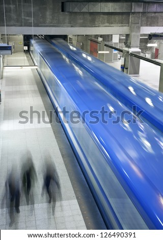 You can see a perfect moment for a picture. 2 metros are in movement and 3 people are at the right place at the right moment for a perfect shot. One of the biggest Montreal underground metro station. - stock photo