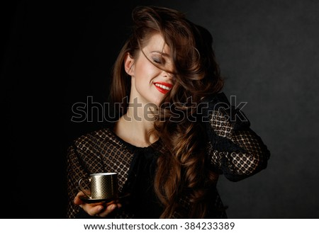 You can't go wrong with cup of barista made good Italian coffee. Happy woman with long wavy brown hair and red lips holding cup of coffee on dark background