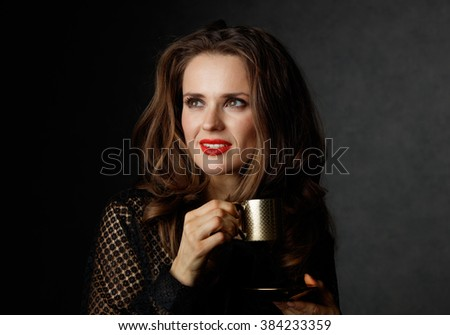 You can't go wrong with cup of barista made good Italian coffee. Woman with long wavy brown hair and red lips holding cup of coffee and looking on copy space on dark background