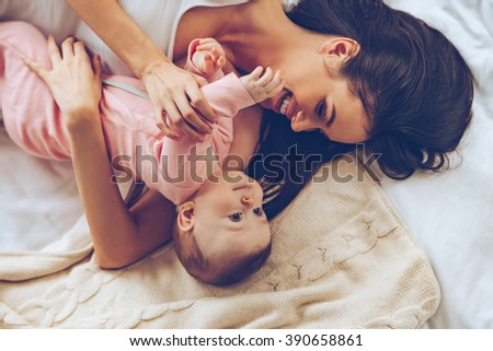You do not want to hug with mommy? Top view of cheerful beautiful young woman hugging her baby girl while lying in bed  - stock photo