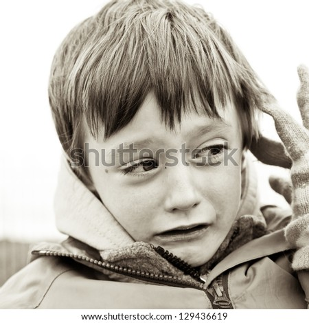 You g boy sad or scared in sepia tones - stock photo