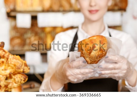 You gonna love it! Selective focus on a fresh bread bakery worker holding out to the camera closeup cropped shot - stock photo