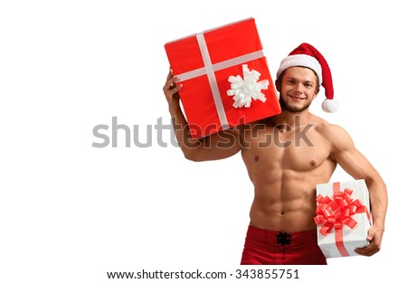 You gonna love it. Young naked man with abs wearing Santa Claus hat holding presents on white background with a copyspace on the side - stock photo