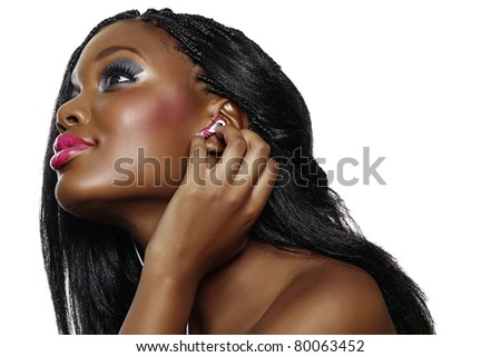 You happy South African woman with beautiful makeup listening to music on earphones over white background - stock photo