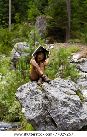 You never know when you might need a laptop... Young women sitting on a rock in the forest, covering herself with a laptop - stock photo