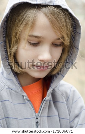 You preteen boy wearing a hoodie and feeling down - stock photo