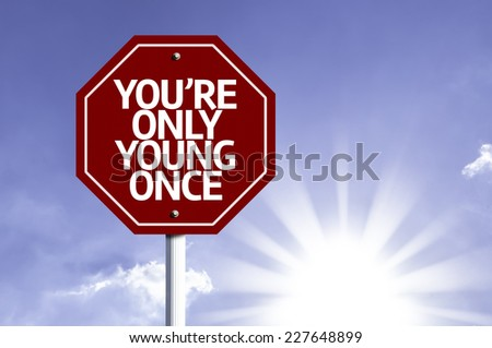You're Only Young Once written on red road sign with a sky on background - stock photo