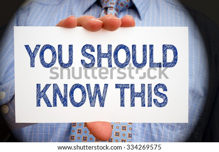 You should know this - Businessman with white sign and blue text - stock photo