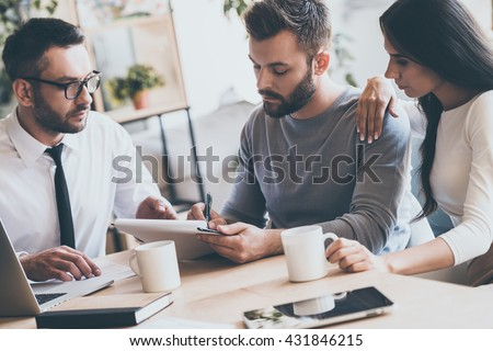 You should sign here. Confident young man signing some document while sitting together with his wife and man in shirt and tie  - stock photo