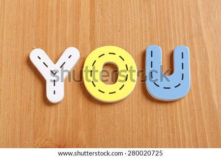 YOU, spell by woody puzzle letters with woody background - stock photo