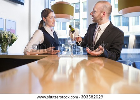 Youg man having breakfast at a bar. He has a digital tablet and is smiling at the camera whilst holding his coffee. - stock photo