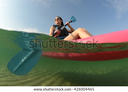 Youg woman wearing life vest in pink kayak - stock photo