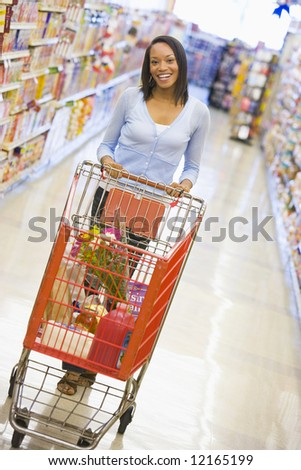 Youing woman grocery shopping in supermarket - stock photo