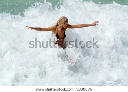 Youing woman play in waves