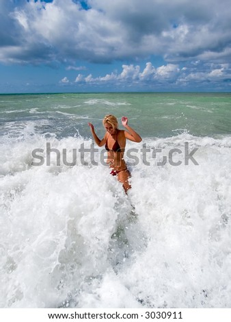 Youing woman play in waves - stock photo