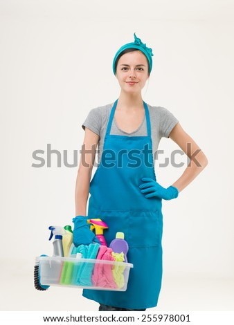youn beautiful maid standing and holding cleaning supplies getting ready for work. isolated on white background - stock photo