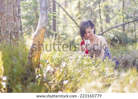 youn mother breastfeeding her baby in the forest in springtime  - stock photo