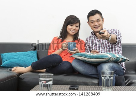 Yound and happy Chinese couple hanging out together at home watching TV