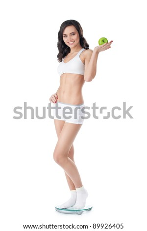 Yound fit girl standing on scales - stock photo