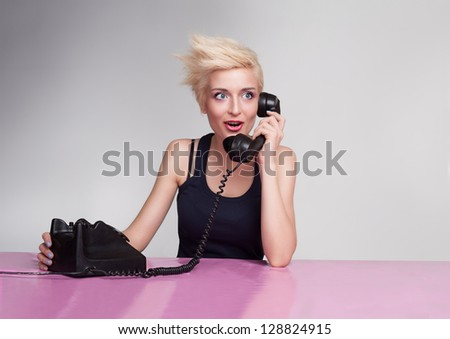 yound lady with blond short hair and blue eyes gossiping on the phone - stock photo