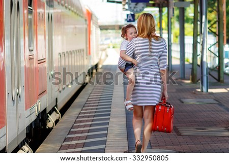 Yound woman and little girl, lovely daughter, on a railway station. Kid and woman waiting for train and happy about a journey. People, travel, family, lifestyle concept - stock photo