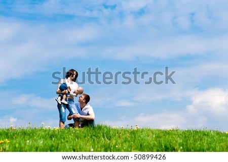 Younf cheerful parents playing with their offspring - stock photo