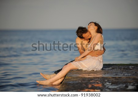 Younf man kissing his girlfriend on a pier