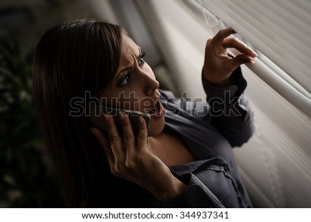 Young abused woman scared looking through the window seeking safety. - stock photo