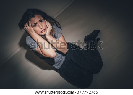 Young abused woman terrified looking with arms in her hair seeking safety. - stock photo