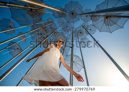 Young active and happy woman having fun on the blue modern abstract background with umbrellas.