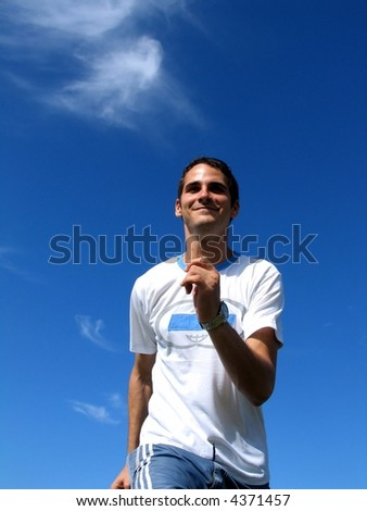 Young active boy running against blue sky
