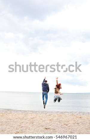 Young active couple joyful jumping up high together on winter holiday beach, nature outdoors. Fun energy recreational lifestyle, enjoying travel vacation, exterior. Carefree healthy well being.