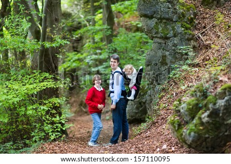 Young active father hiking in a beautiful autumn cliff and forest landscape with his school age son and baby daughter sitting in a back carrier - stock photo