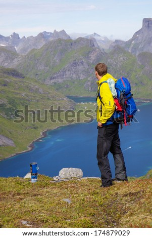 Young active hiker with backpack looking at scenic view on Lofoten islands in Norway on sunny day - stock photo